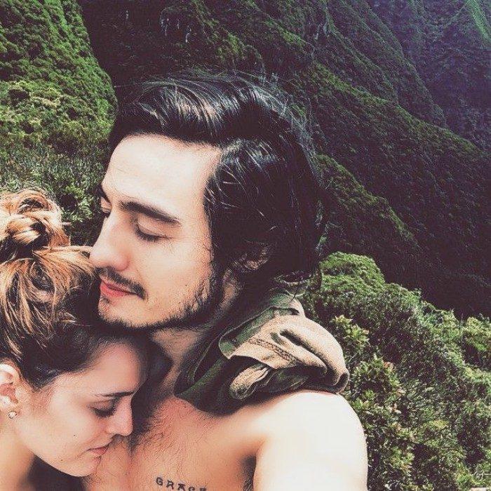 pareja en paisaje de montañas abrazados con ojos cerrados