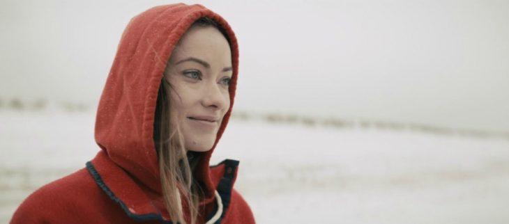 mujer sonríe con sudadera y capucha roja