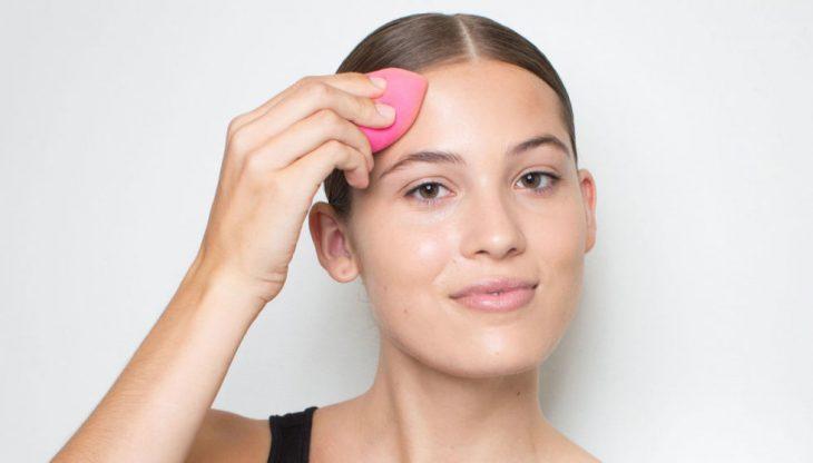 mujer con esponja de maquillaje