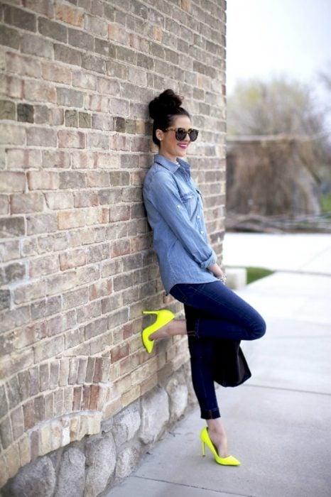 mujer recargada en la pared con tacones color neon
