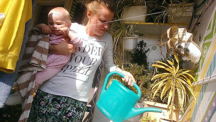 madre regando las plantas y cargando a su bebe