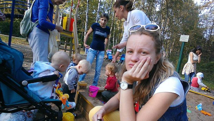 madre aburrida en el parque con su bebe y mas niños