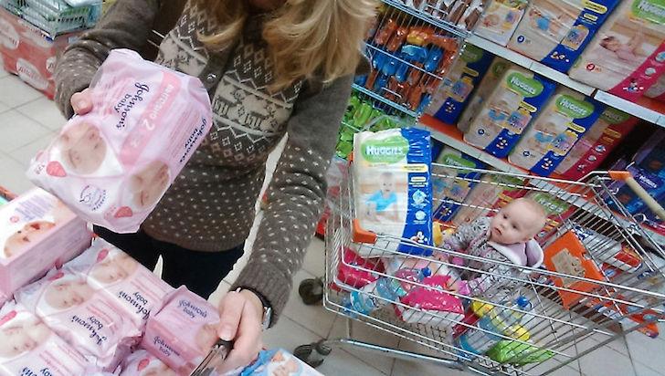 madre comprando pañales y bebé en carro de super
