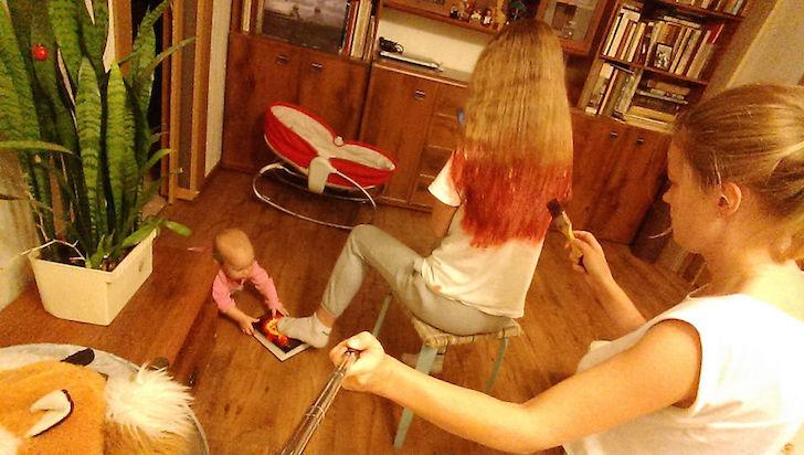 madre pintando cabello de hija y bebe en el suelo