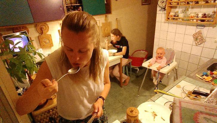 madre comiendo, atras hija comiendo y bebe en silla