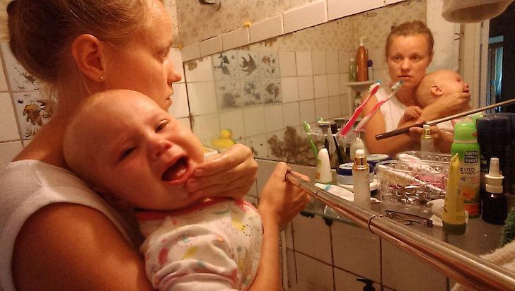 madre con bebe enfrente de baño de espejo