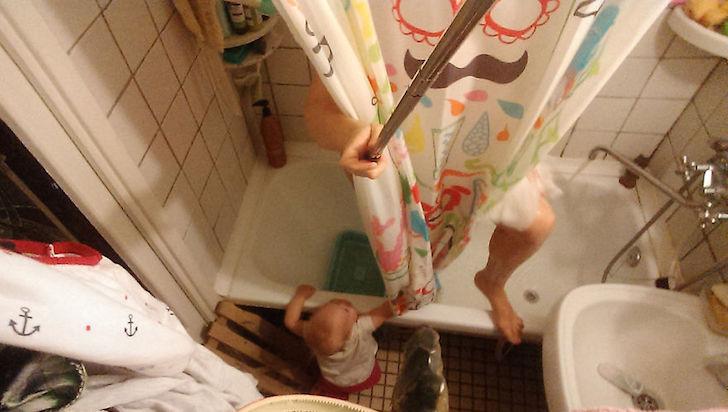 madre saliendo de bañarse y bebe afuera de tina de baño