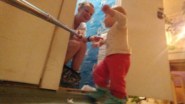 madre en el baño con selfie stick y su bebé
