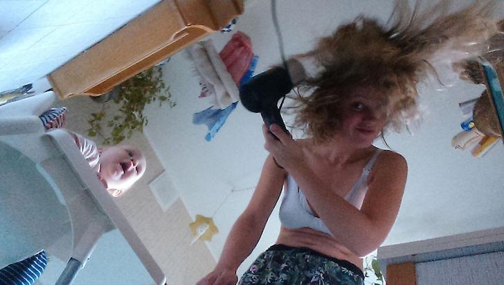 madre agachada se seca el cabello con secadora