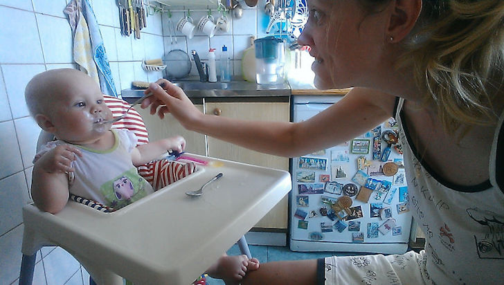 madre le da de comer a su bebe y hace cara graciosa