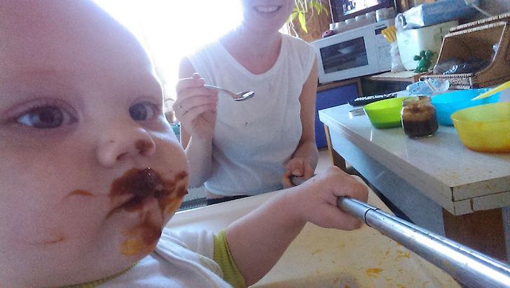 bebe manchado de comida y madre en la cocina