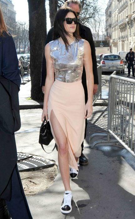 mujer caminando con falda color durazno y blusa plata