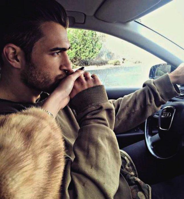 hombre besándo la mano de mujer en el coche