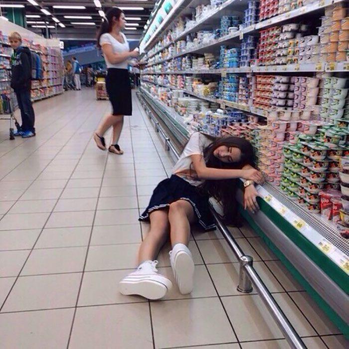 mujer en el suelo de pasillo de super mercado cansada