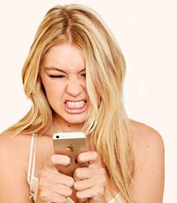 mujer rubia con celular en la mano enojada