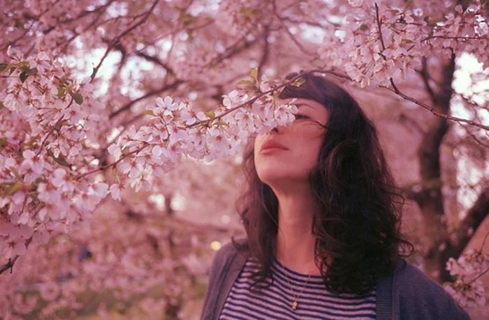 chica con flores rosas en un arbol oliendo