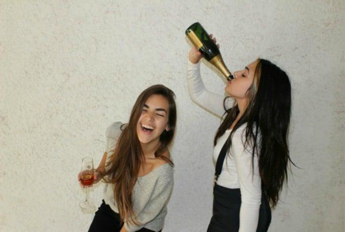 amigas tomando de botella de vino riéndo