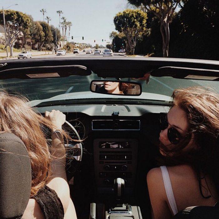 dos mujeres manejan en la ciudad con convertible