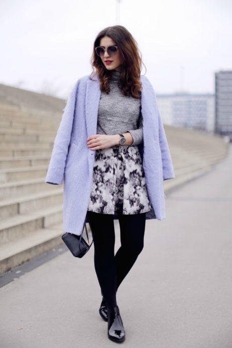 mujer de pie con saco lila y medias negras