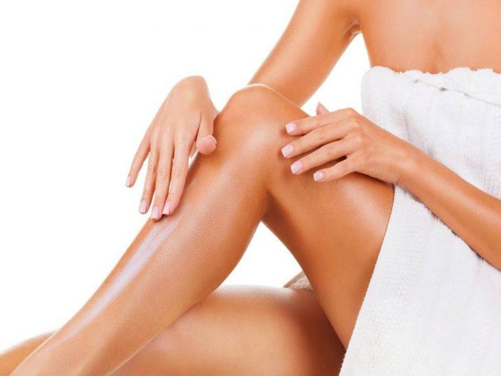 mujer aplicando crema en sus piernas