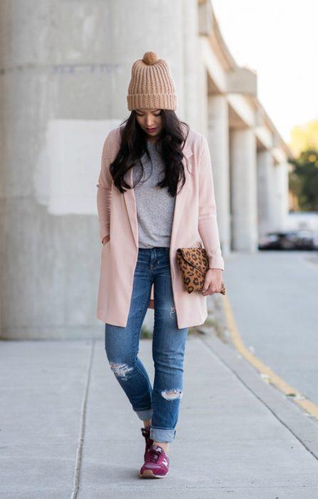 mujer caminando en la calle con gorro y saco rosa pastel