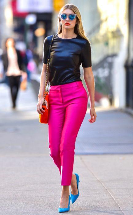 mujer rubia caminando en la calle pantalon rosa y camisa negra