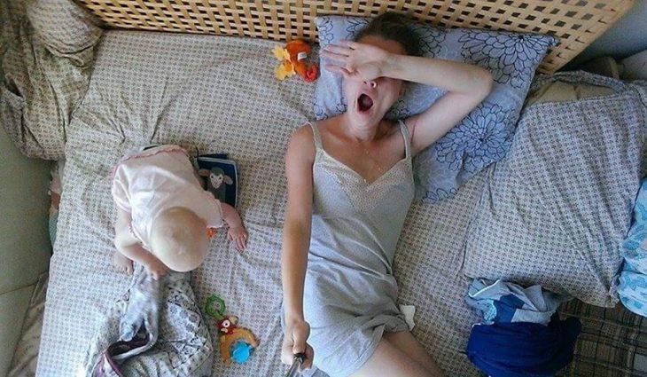 madre se despierta bostezando y bebe a un lado
