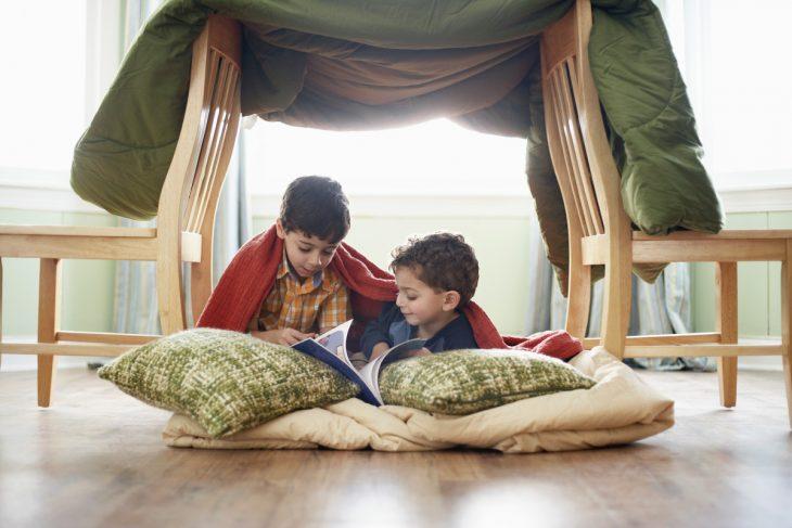 niños en el suelo leyendo con almohadas