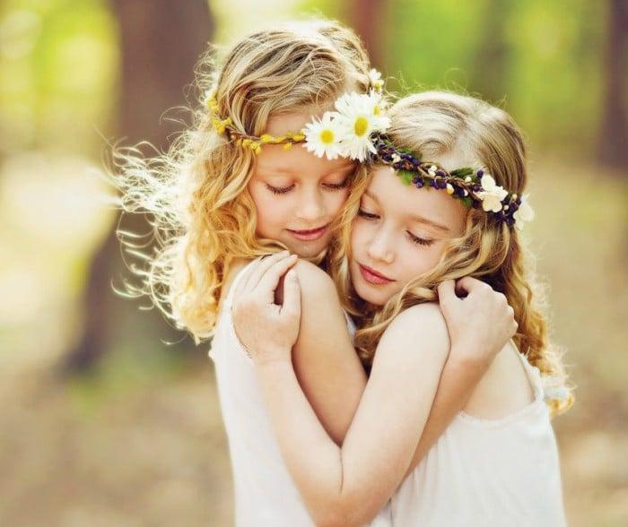 dos niñas rubias con diademas de flores abrazandose
