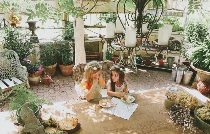 dos niñas sentadas en la mesa con plantas