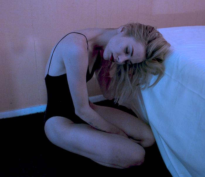 chica sentada al lado de la cama despierta escuchando voces