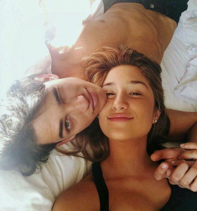 Chica y hombre en la cama sonrién