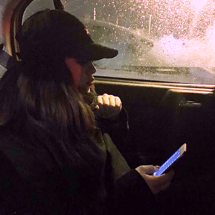 chia de noche en coche con celular en la mano