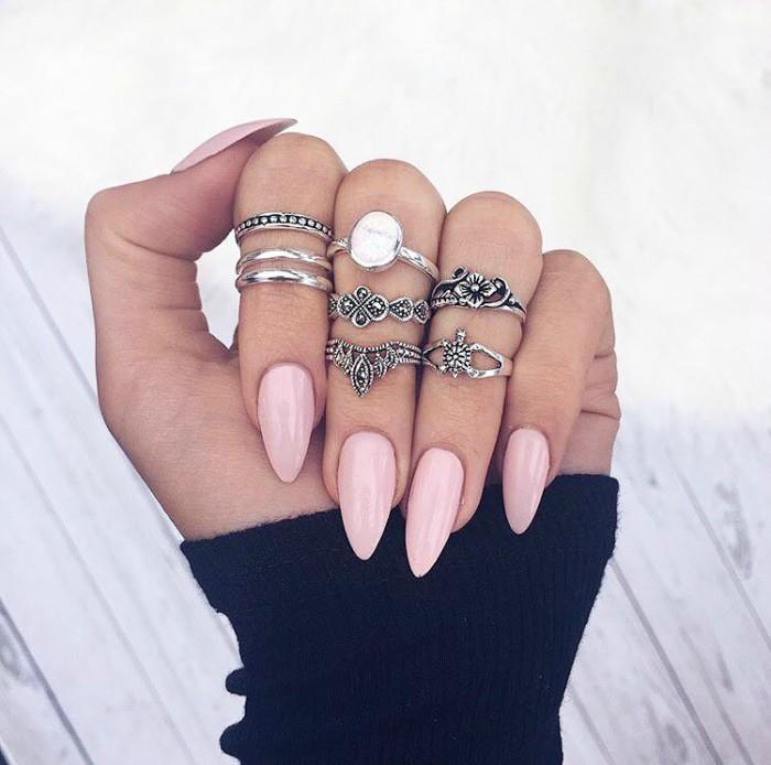 mano con unas color rosa y muchos anillos