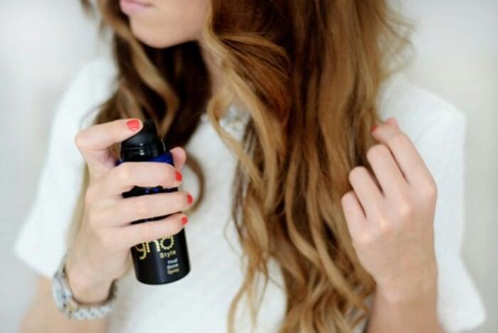 chica rociando spray en su cabello