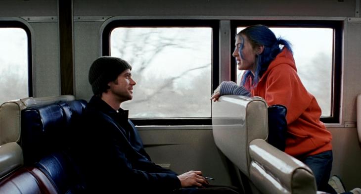 hombre sentado en tren y mujer de cabello azul en frente