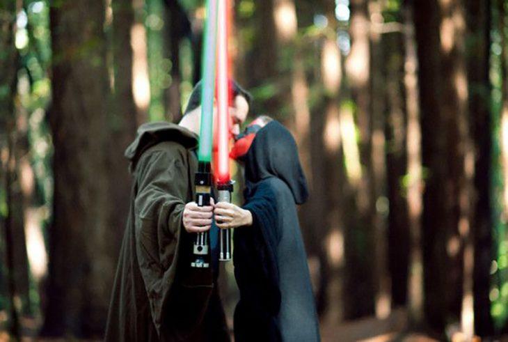 pareja vestidos de star wars se dan beso y espadas de laser