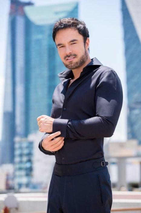 Alejandro lópez, actor, posando para una revista con camisa negra y pantalón a juego