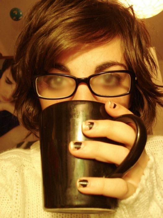 chica tomando bebida caliente con lentes empañados
