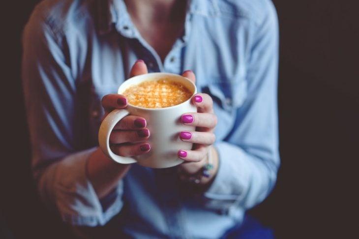 chica con bebida caliente en la mano