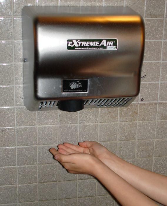 mujer calentándose las manos en secador de manos de aire