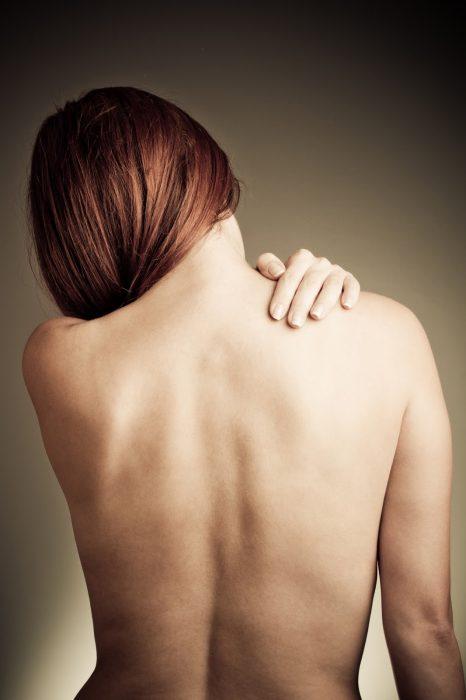 mujer espalda desnuda se toca con la mano