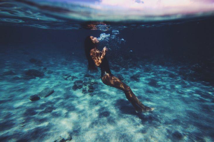 Chica en el fondo de una piscina nadando