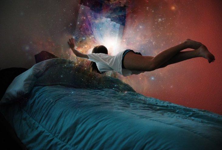 Chica flotando sobre su cama mientras ve una galaxia