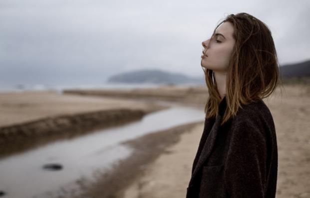 Chica parada viendo hacia un lago