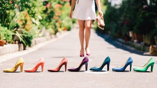 chica caminando con zapatos de tacón en la mano