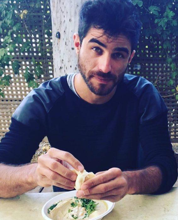 hombre con camisa azul comiendo con las manos