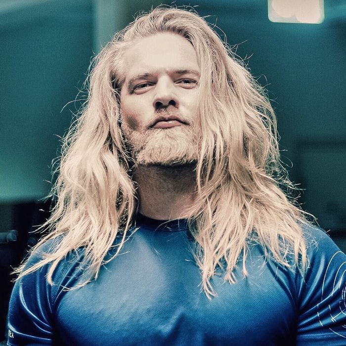 hombre rubio playera azul barba tupida