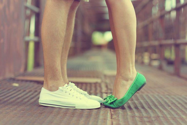 pareja él alto ella bajita de puntitas