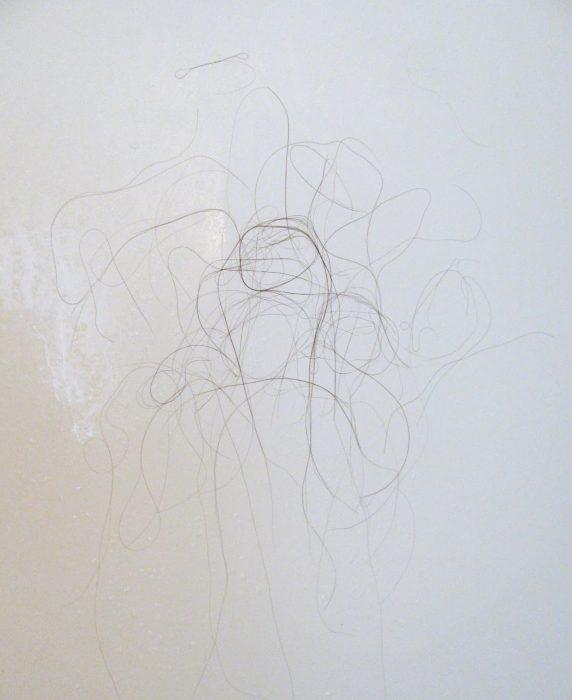 cabellos oscuros en el piso del baño
